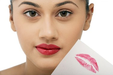 Woman holding a peice of paper with lipstick imprint
