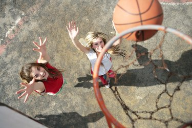 Two young women playing basketball