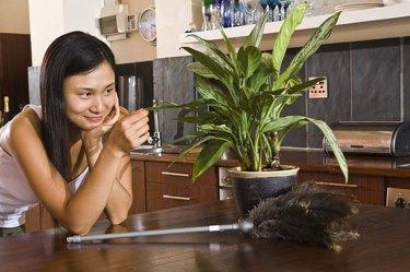 Woman looking at plant at home