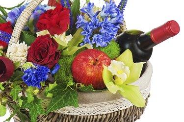 Flower arrangement of roses, orchids, fruits.
