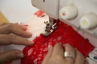 Tailor at sewing machine tailoring lingerie or a bra