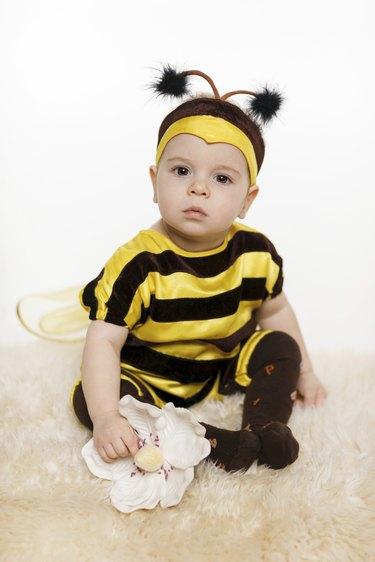 Baby wearing bee costume sitting on the floor