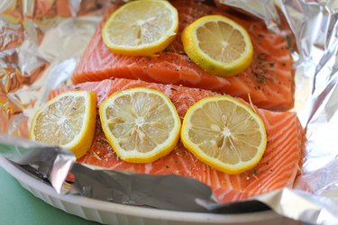 Two salmon fillets on a sheet of foil with seasoning and lemon.