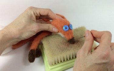Female hands needle felting a brown nose onto a fox face.