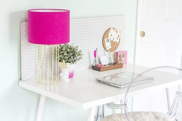 Modern desk with a pink lamp and a clear chair