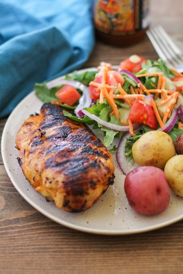 Grilled chicken on  a plate with potatoes and salad