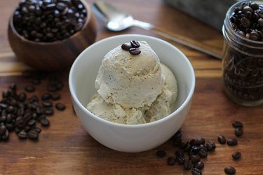 Bowl of coffee ice cream with a few whole beans on top.