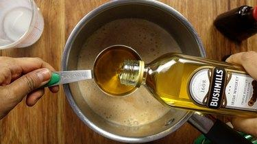 Adding whiskey into saucepan for sugar-free Irish cream liqueur.