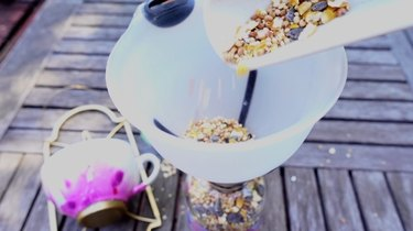 Filling DIY bird feeder made from wrought iron candle sconce and teacup.