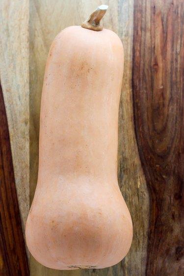 Whole butternut squash on a cutting board.