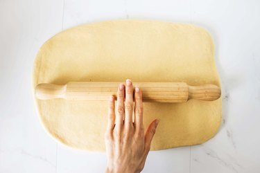 Rolling the dough into a rectangle shape.