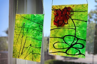 Two yellow and green melted crayon sun catchers hanging in a sunny window