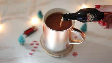 Pouring Irish cream liqueur into hot cocoa