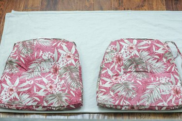 Patio cushions lined up along the folded drop cloth