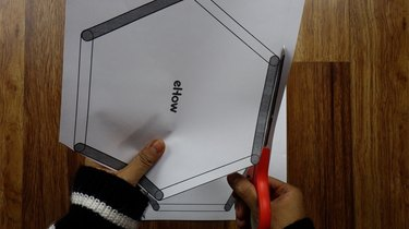 Cutting out templates to make popsicle stick hexagon shelves.