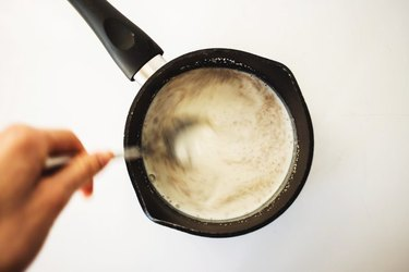 Whisking together the milk and yeast.