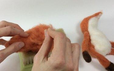 Female hands needle felting an orange mass of wool roving.