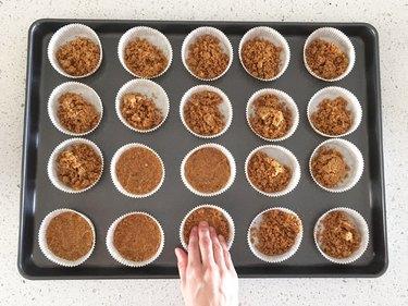 Pressing graham cracker crust into cupcake cups