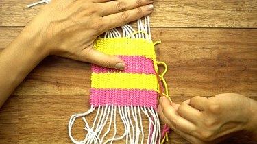 Weaving in loose yarn tails for DIY coasters on a cardboard loom.