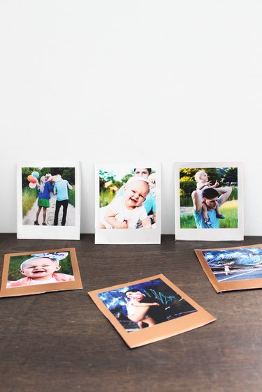 Photos propped against a wall.