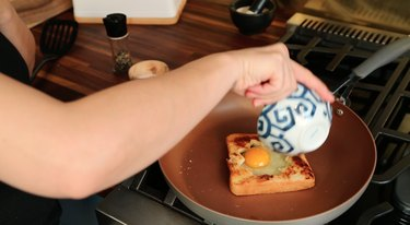 sliding raw egg into toast