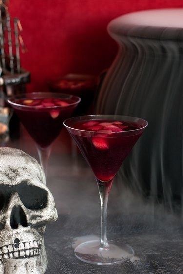 Close up of a class of sangria with smoking cauldron behind it