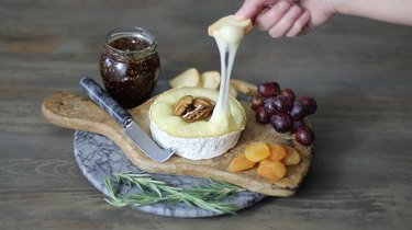 dipping cracker into warm brie