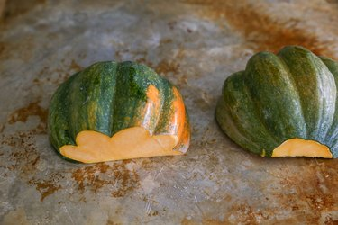 acorn squash face-down on a baking sheet
