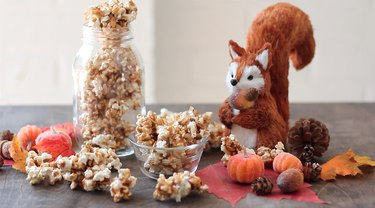 Pumpkin spice caramel corn displayed with mini pumpkins, acorns, and a squirrel figure.