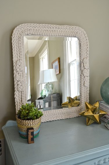 Knotted rope mirror displayed in room.