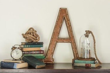 """A letter """"A"""" leather monogram next to stacks of books"""