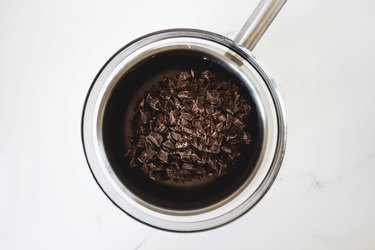 Finely chopped dark chocolate set in a heatproof bowl and saucepan.