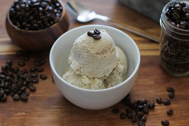 A white bowl with three scoops of coffee ice cream and two jars of coffee beans