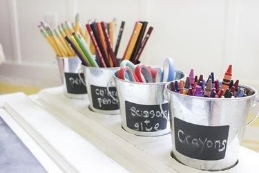 Tin buckets with school supplies inside.