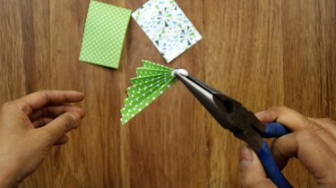 Pinching glued end of paper Christmas tree to secure.