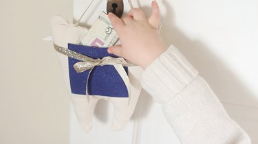 Child's hand grabbing money out of pouch
