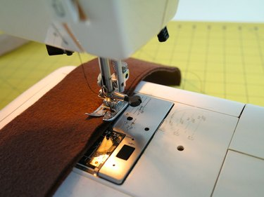 A sewing machine sewing the sides of the tail.