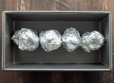 Four whole beets wrapped in foil on a baking sheet.