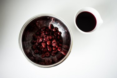 A large bowl of cooked cherries next to a small bowl of cherry-liqueur syrup.
