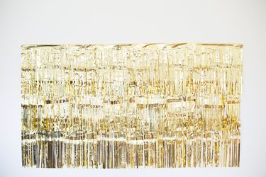 Gold photo backdrop with three rows of garland