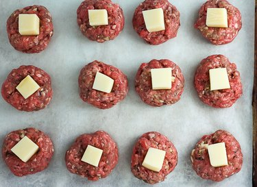 Raw meatballs with a cube of cheese pressed into the top of each.