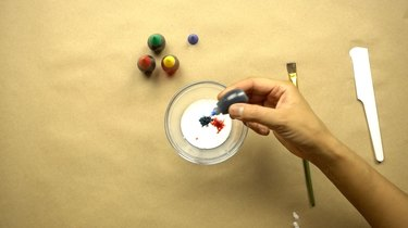 Adding food coloring to glue to create a faux sea glass effect on glass decor.