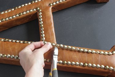 """Point of nailhead trim where nail is driven is is lined up with corner of inside 'leg' of letter """"A""""."""