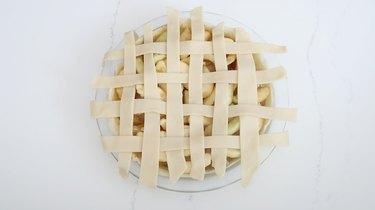 Strips of dough woven into lattice pattern on pie