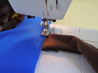 A sewing machine attaching the tail to the vest.