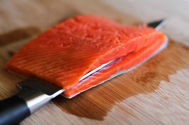 Salmon being cut by a knife.