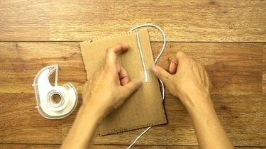 Warping a cardboard loom to make DIY coasters.