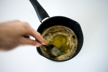 Hand stirring butter and vanilla mixture in a hot saucepan.