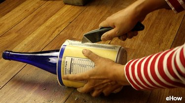 Removing plastic mold from DIY concrete tabletop tiki torches out of used glass bottles.