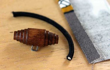 Wooden toggle and hair elastic for closure.